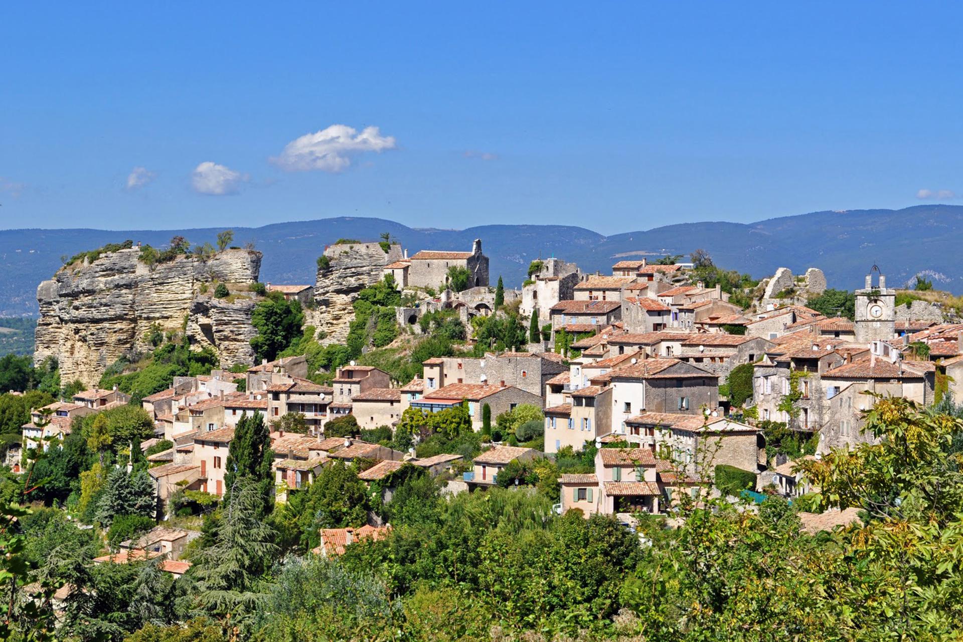 Village typique du sud de la France, maisons en pierre à flanc de colline au milieu de boisés