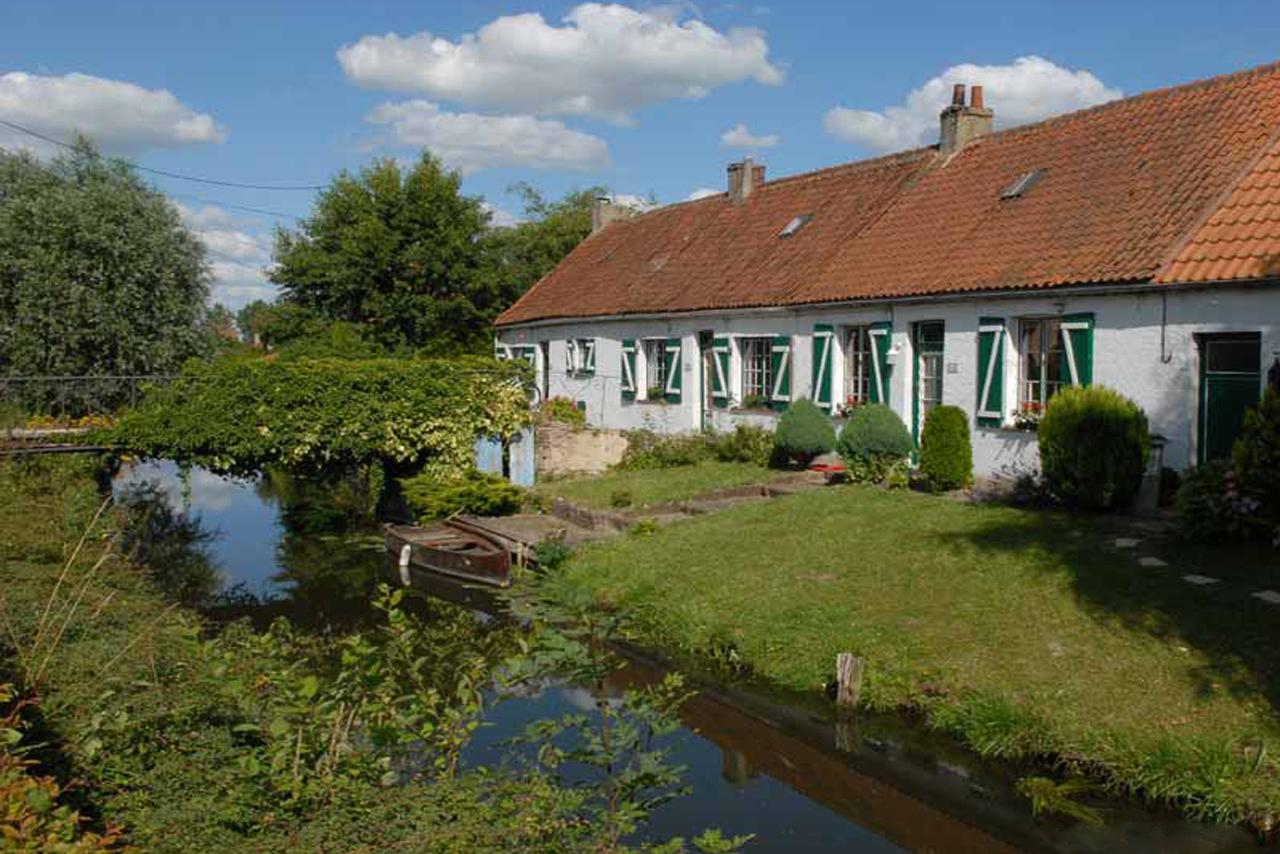 Maison blanche à volets verts au bord d'un petit canal en été sur lequel un canot est attaché, un petit pont surmonte le canal