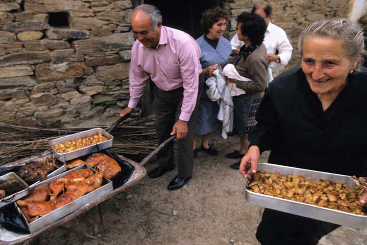 Five smiling people in front of a stone house, and a man and a woman carrying traditional dishes