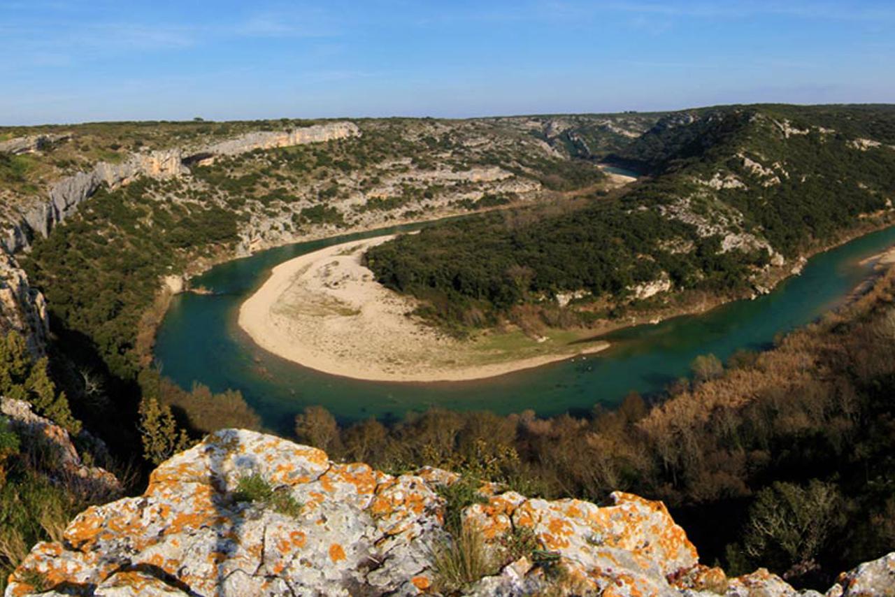 Rivière d'une eau turquoise formant une boucle entre les collines de maquis environnantes