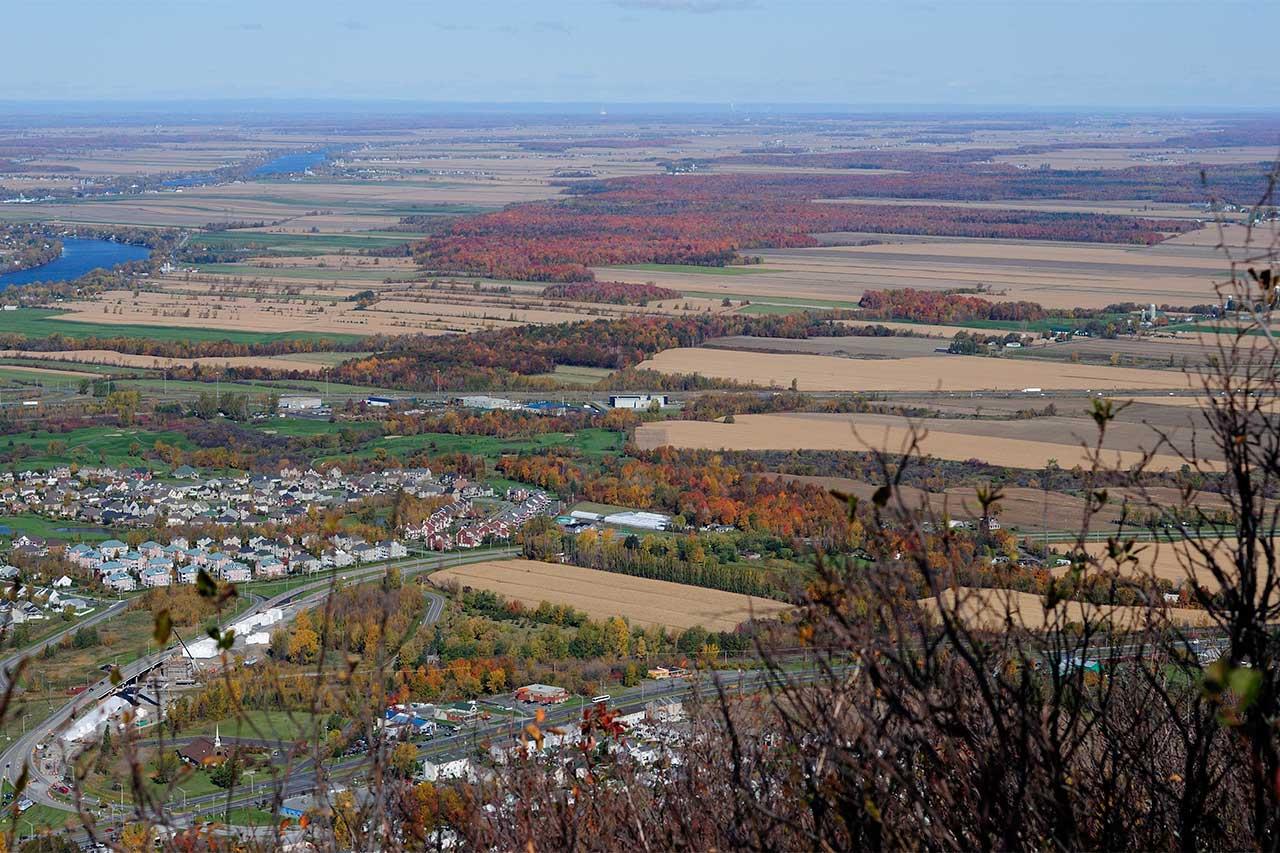 Vue depuis un des sommets du mont Saint-Hilaire sur la plaine et la rivière Richelieu, les corridors forestiers sont au milieu des champs agricoles en automne