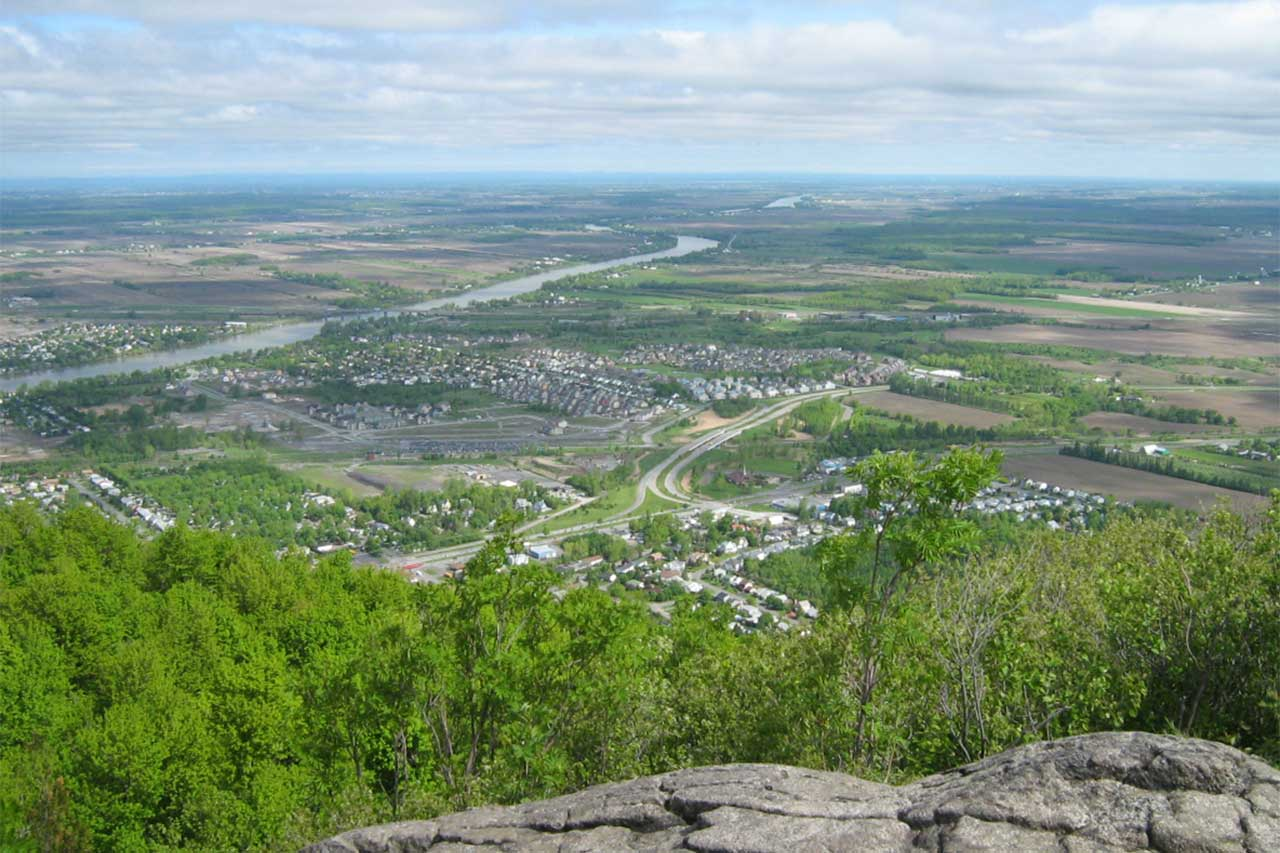 Vue depuis un des sommets du mont Saint-Hilaire sur la plaine et la rivière Richelieu, les corridors forestiers sont au milieu des champs agricoles en été