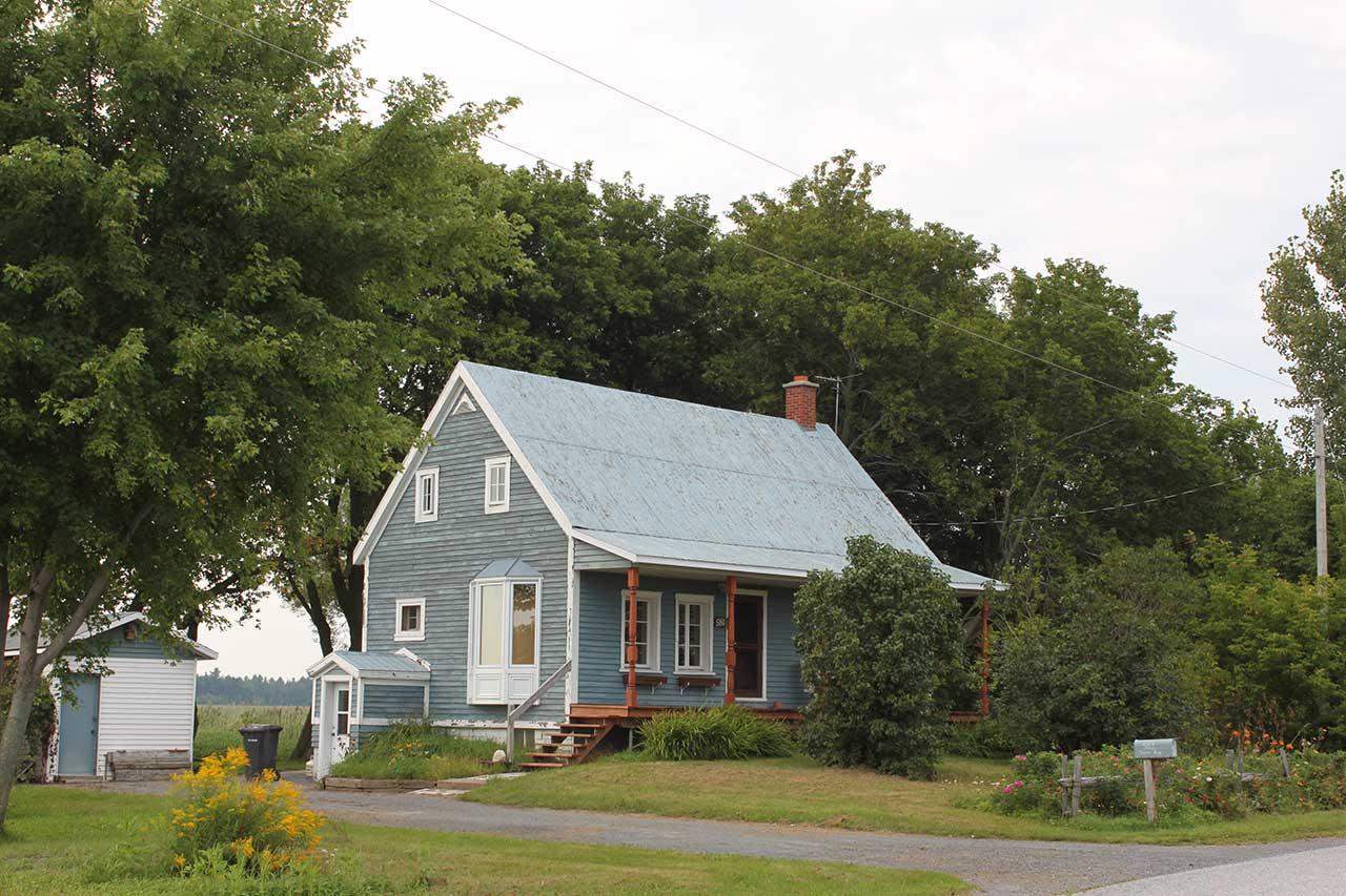 Petite maison bleue en bois sur un terrain boisé et fleuri le long d'une route