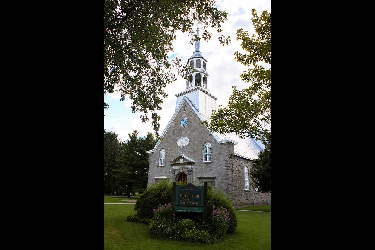 Église de La Présentation sur un terrain bien entretenu, fleuri et boisé