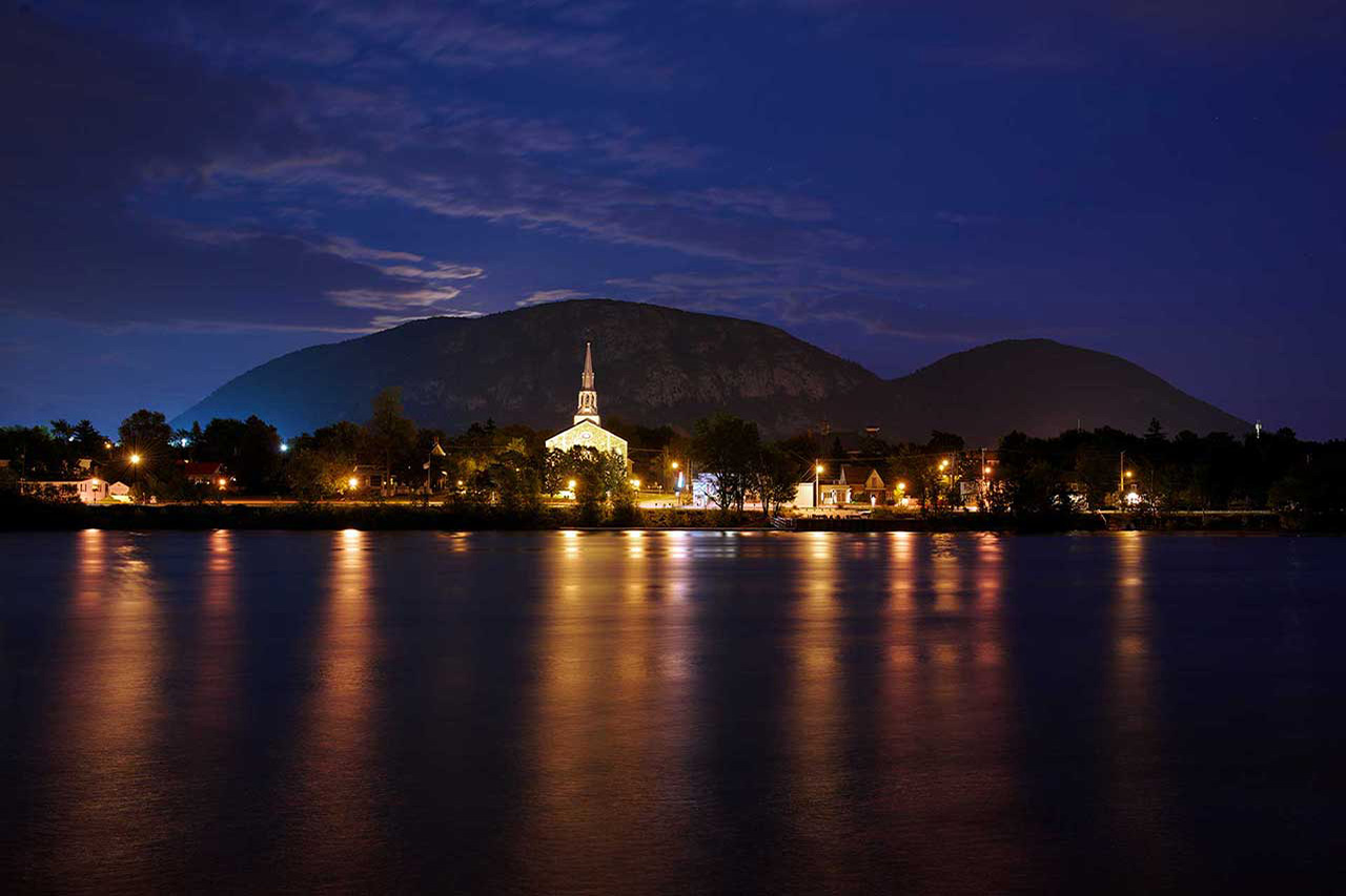 Vue depuis Beloeil sur la rivière Richelieu, la rive illuminée de Mont-Saint-Hilaire et son église et sur le mont Saint-Hilaire de nuit