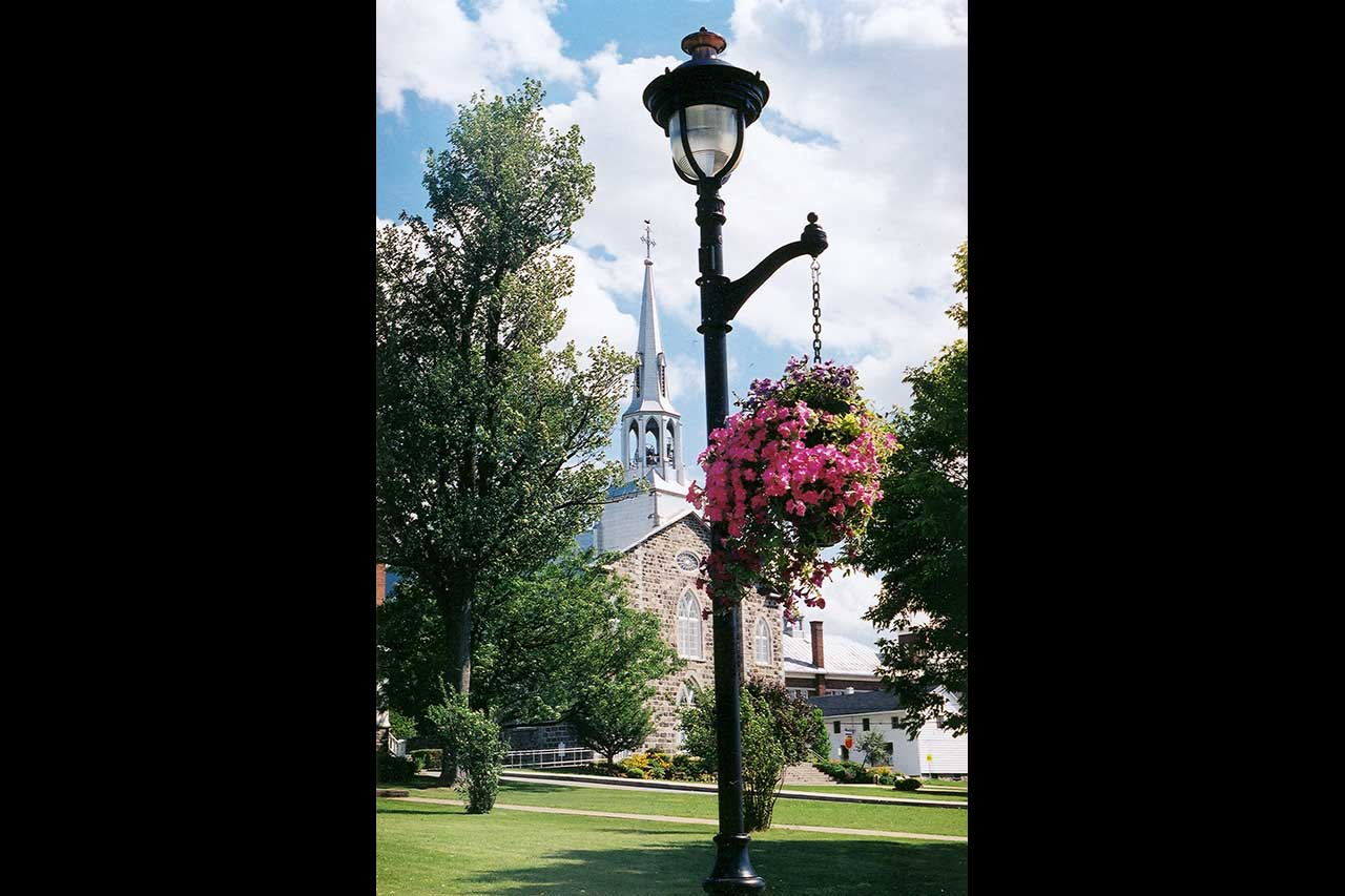 Église de Mont-Saint-Hilaire de jour entourée d'un parc arboré et fleuri