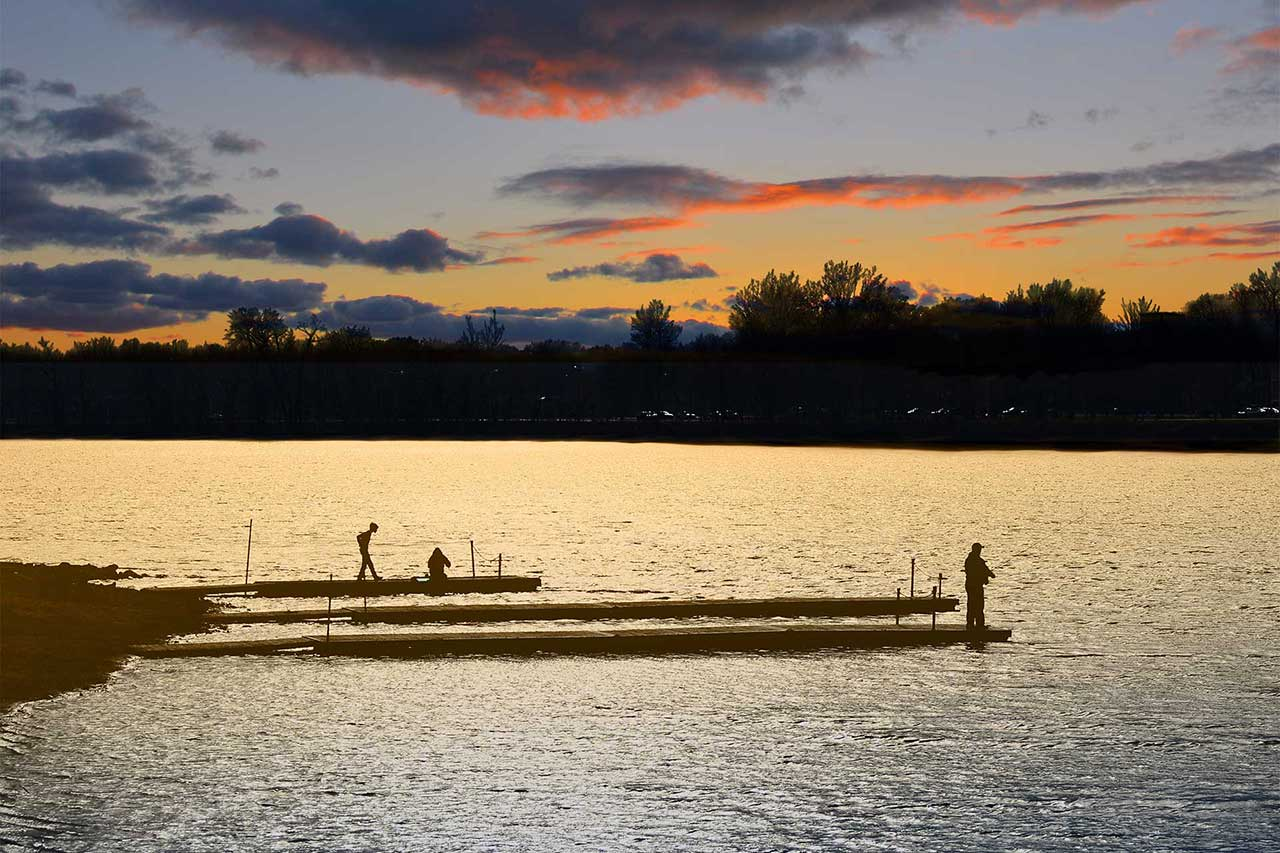 Berge de la rivière Richelieu au soleil couchant, un homme est en train de pêcher, deux autres personnes sont au bord de l'eau