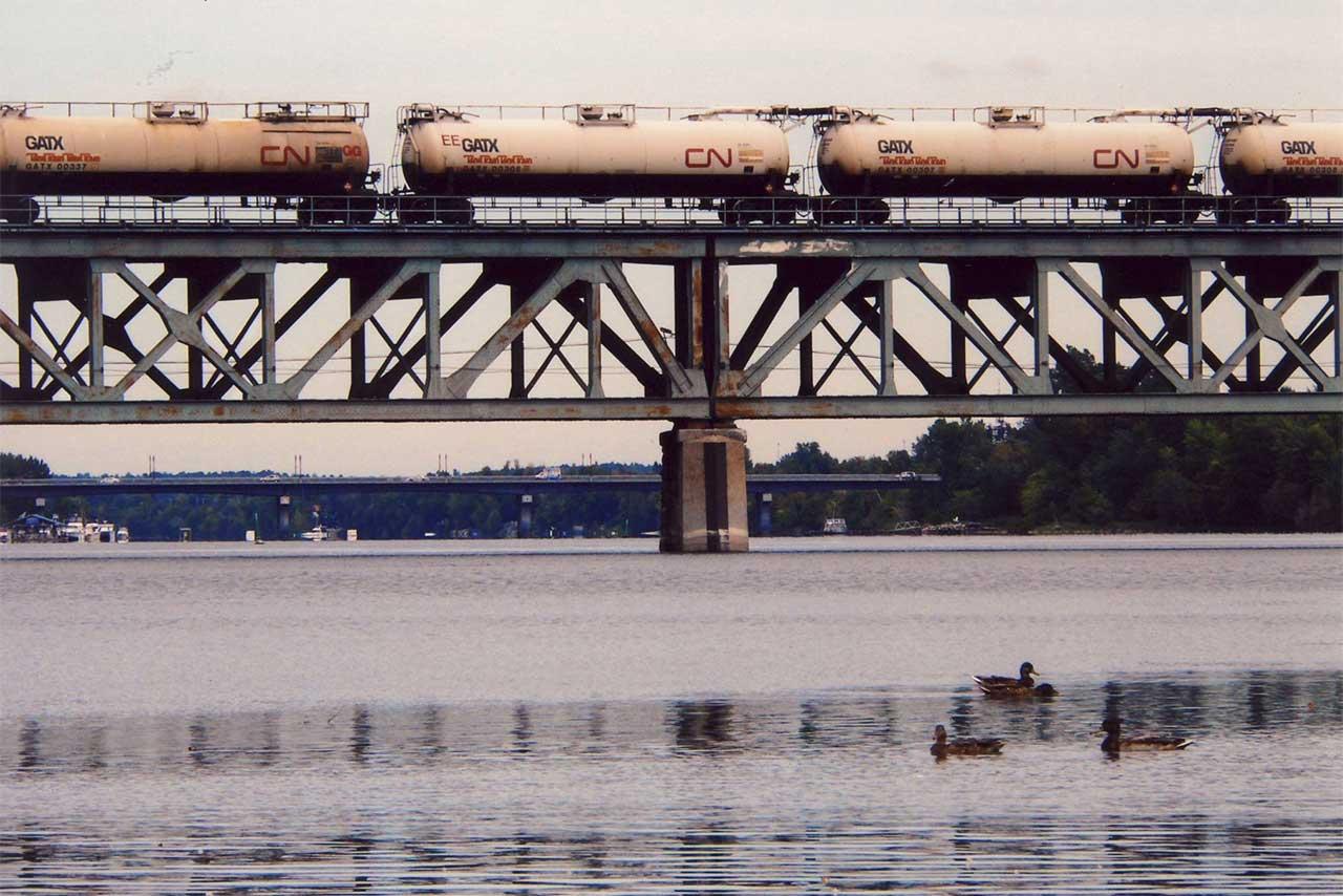 Wagons sur la voie ferroviaire au-dessus de la rivière Richelieu, quelques canards sont sur l'eau