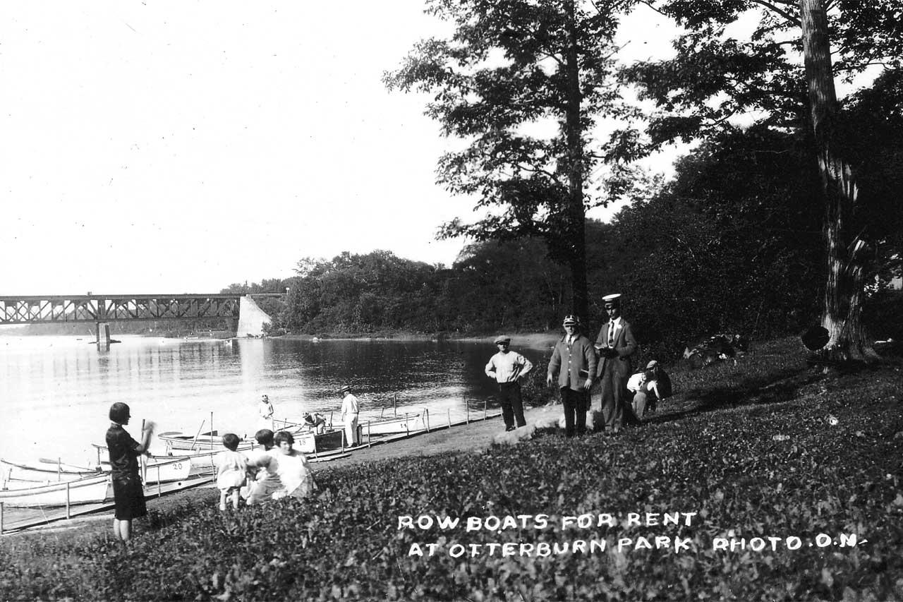 Ancienne photographie en noir et blanc représentant des familles près des locations de canots sur les berges de la rivière Richelieu