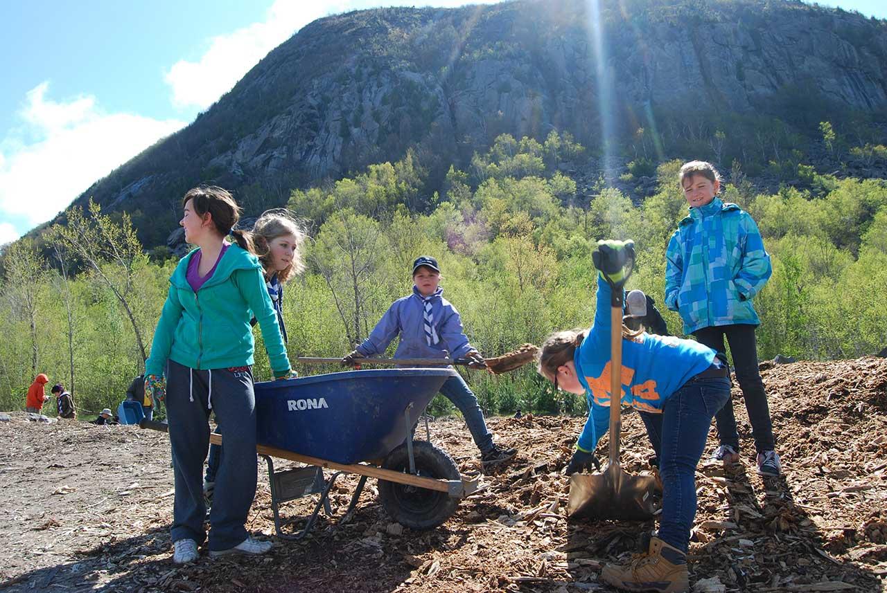 Cinq enfants autour d'une brouette en train de creuser la terre afin de planter des arbres, vue sur la falaise du mont Saint-Hilaire