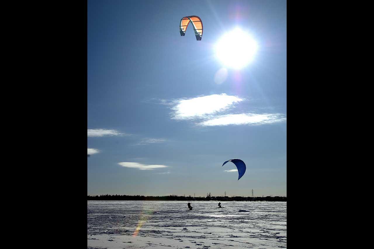 Deux personnes faisant du kitesurf sur la rivière Richelieu gelée en hiver