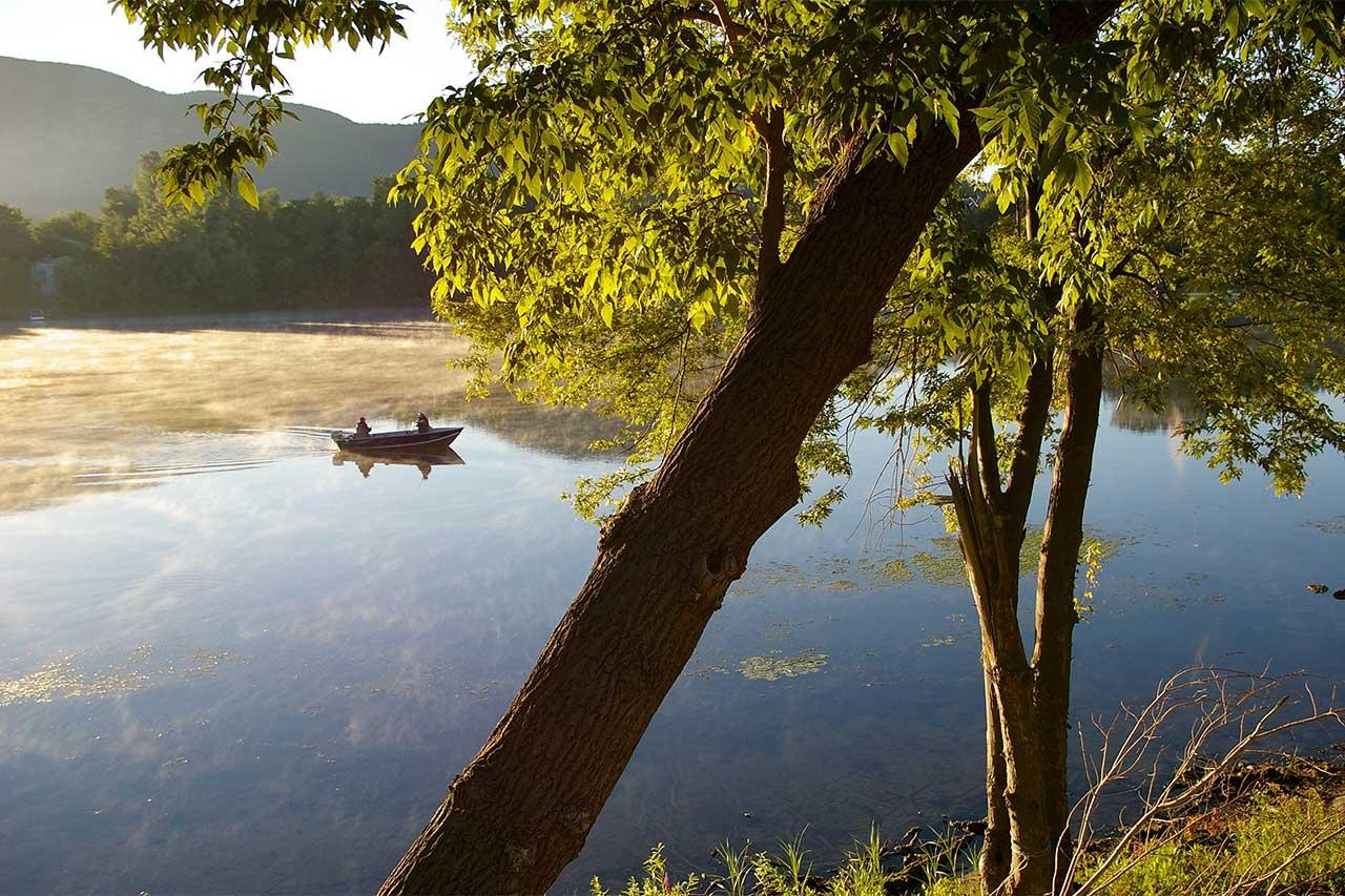 photo description iciVue depuis une berge abritée d'arbres, deux personnes dans un canot au milieu de la rivière Richelieu encore embrumée