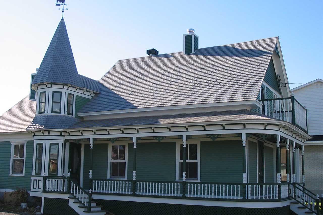 Maison de ville verte et blanche en bois avec colonnes