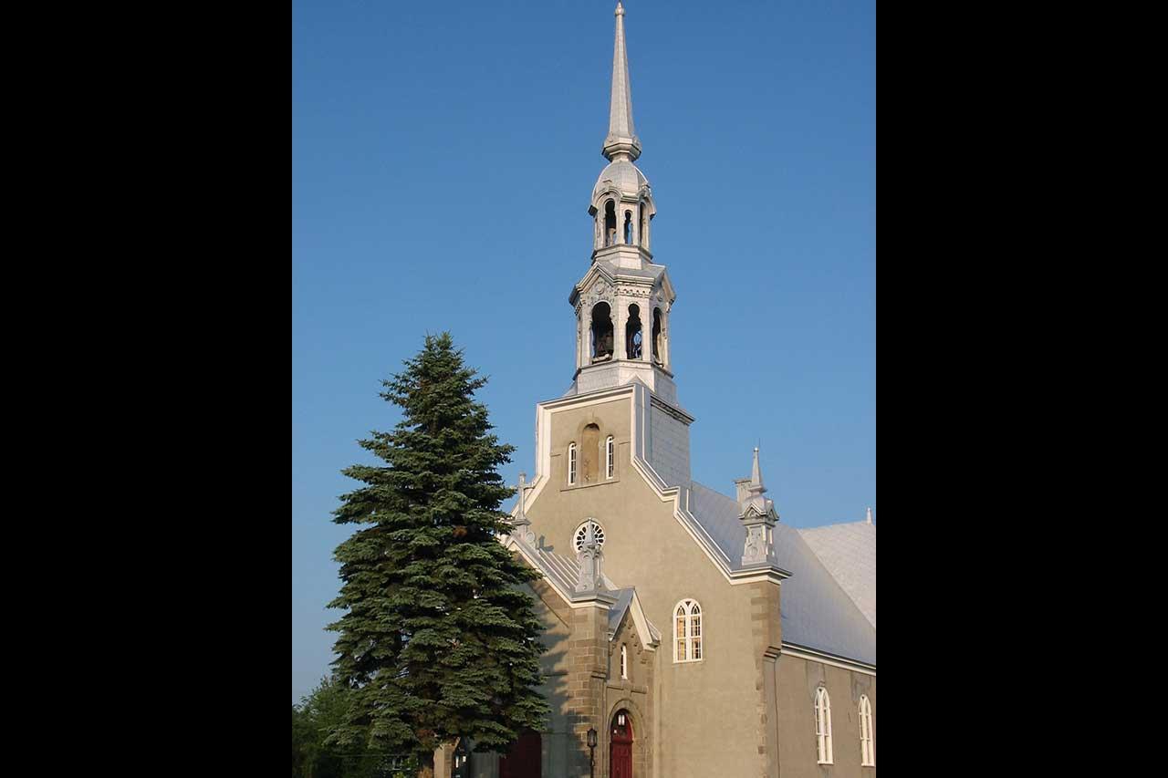 Église de Saint-Jean-Baptiste devant laquelle se trouve un grand sapin