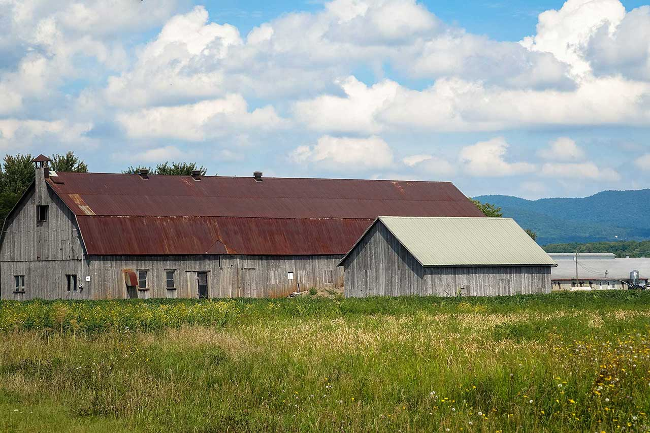 A small wooden barn with a grey roof and large wooden barn with a brown roof in a prairie