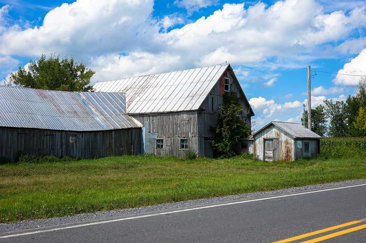Old three-piece wooden barn by the side of a road