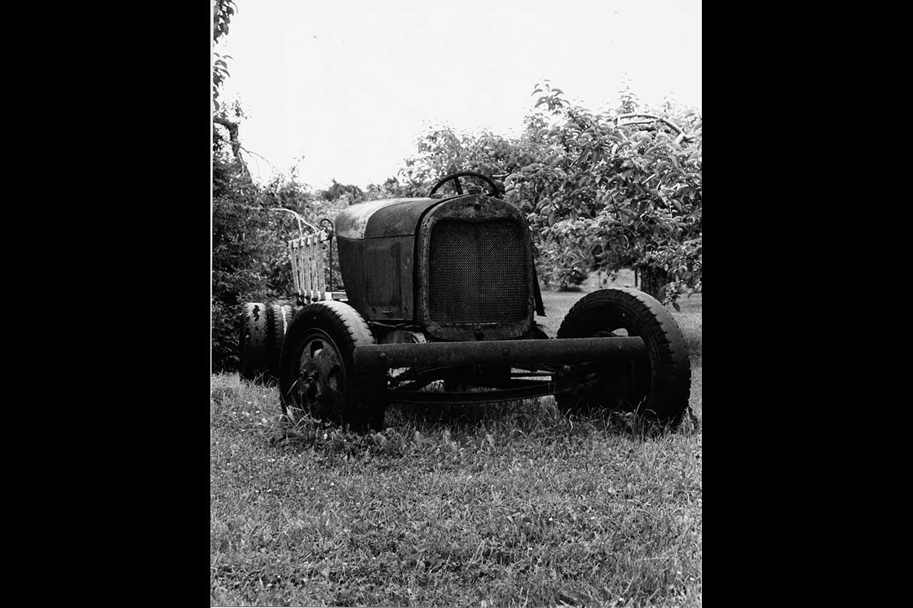 Photographie en noir et blanc d'un ancien tracteur au milieu des pommiers