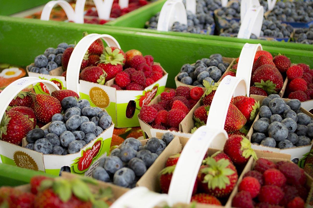 Cardboard baskets of strawberries, blueberries, and raspberries