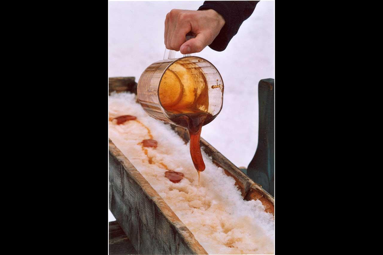 Une personne dont on ne voit que la main verse un pot de sirop d'érable dans un bac en bois remplit de neige pour la tire d'érable
