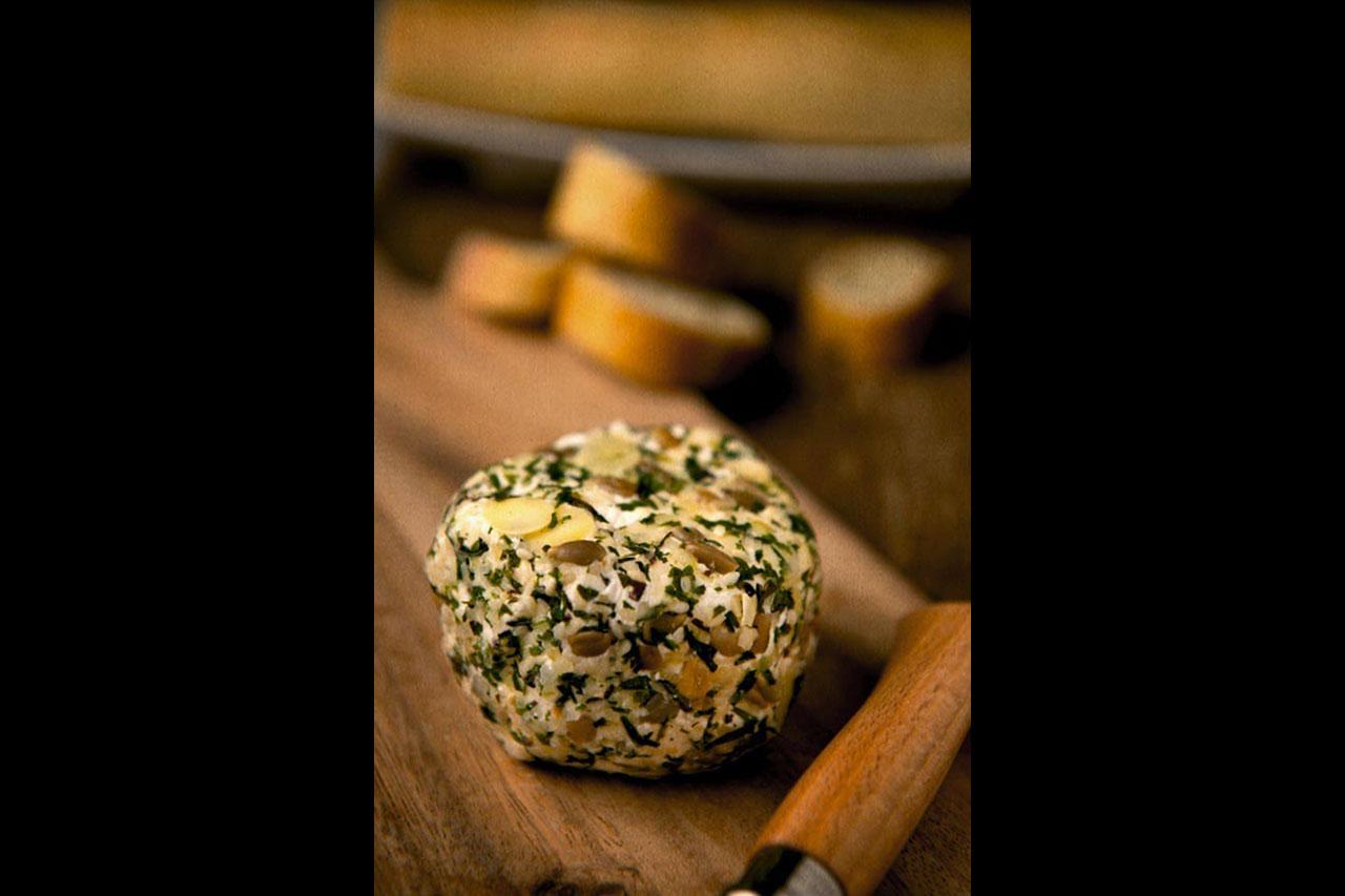 Boule de fromage de chèvre frais aux fines herbes et noix et un couteau à manche en bois posés sur une planche de bois